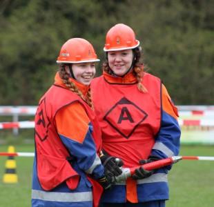 Tatjana und Saskia haben die Wasserversorgung aufgebaut und beginnen mit dem Löschen des simulierten Brandes.