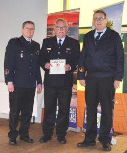 Werner Kley wird durch den stellvertretenden Bezirksjugendfeuerwehrwart Sascha Bädorf und Kreisjugendfeuerwehrwart Klaus Smit verliehen. Foto: Klaus Smit